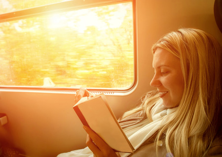 people travelling: Happiness woman reading book in train under sunlight
