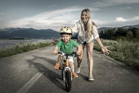 mama e hijo: Felicidad de la madre e hijo en la bicicleta al aire libre