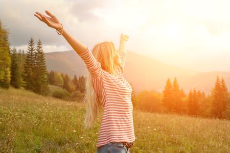 ��smiling: Mujer de la felicidad permanecer al aire libre bajo la luz del sol de la puesta del sol