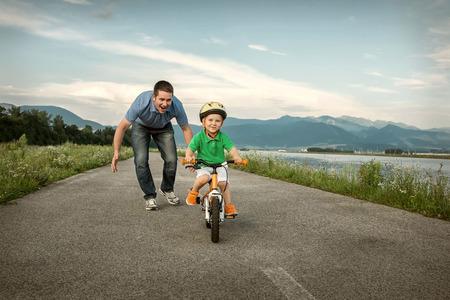 niños en bicicleta: Padre Felicidad e hijo en la bicicleta al aire libre Foto de archivo