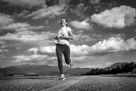 outdoor pursuit: Beautiful female running on road under sky with sun light