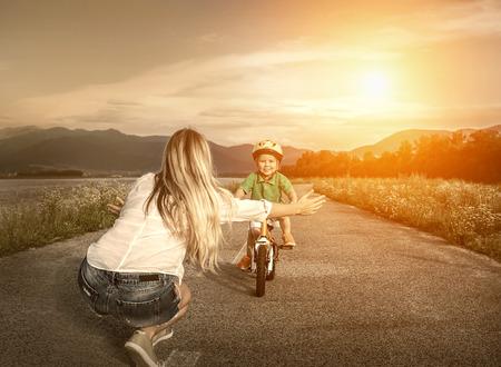 niños en bicicleta: Felicidad de la madre e hijo en la bicicleta al aire libre