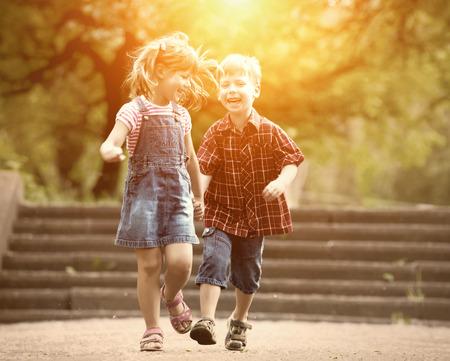 hermanos jugando: Ni�o y ni�a Felicidad diversi�n al aire libre bajo la luz solar Foto de archivo