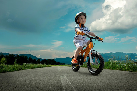 family exercise: Child seating on the orange bicycle and travelling on the non-urban road under sky