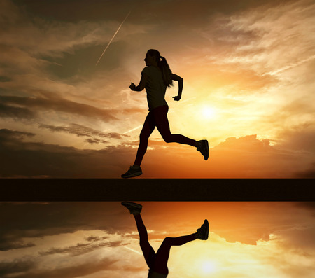 athlete running: Beautiful silhouette of female running on road under sky with sun light and reflection in water