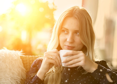 Beautiful blonde female drink coffee under sunlight