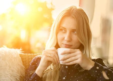 alimentos y bebidas: Hermosa rubia beber café mujer bajo la luz solar