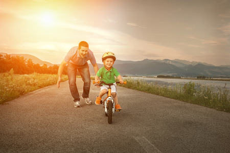 convivencia familiar: Padre Felicidad e hijo en la bicicleta al aire libre Foto de archivo