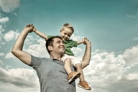 Son seating on the father under beautiful sky with sun photo