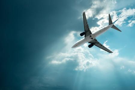 Vliegtuig bij het vliegen onder hemel met wolken