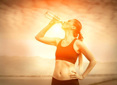 running water: Beautiful female after running, drink water under sky Stock Photo