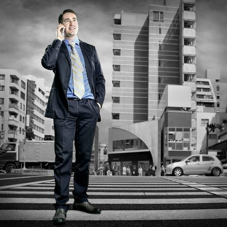 cruce de caminos: Hombre de negocios hablando por tel�fono en la encrucijada Foto de archivo
