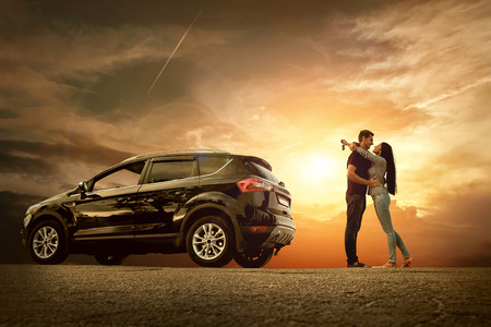 Happiness couple stay near the new car under sky Stock Photo