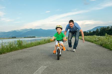 andando en bicicleta: Padre Felicidad e hijo en la bicicleta al aire libre Foto de archivo