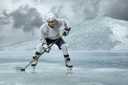 Ice hockey player on the ice in mountains photo