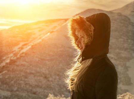 stay beautiful: Woman stay under sun light. Beautiful winter mountains view. Stock Photo