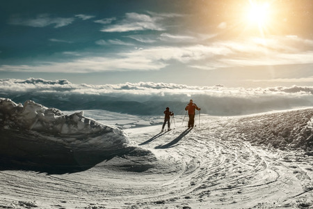 Two skiers on the peak of mountain in sunny day. photo