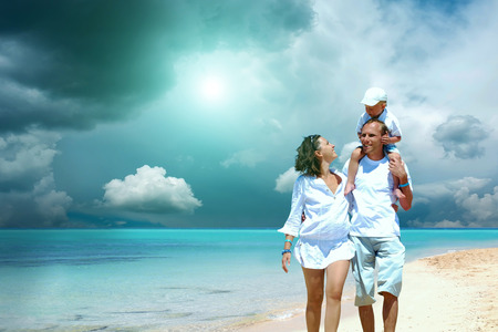 View of happy young family having fun on the beach photo