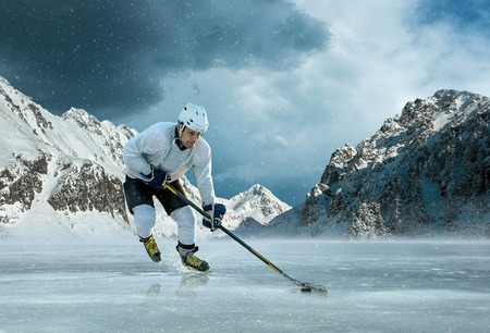 ice hockey player: Ice hockey player in action outdoor around mountains