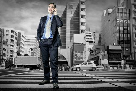 crossing street: Businessman speaking by phone on the crossroad