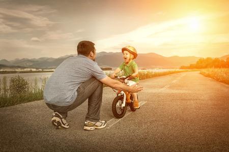 educating: Padre e hijo en la bicicleta al aire libre