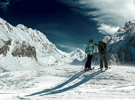Skiers couple looking on the winter mountains in sun day. photo