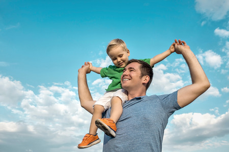 daddy: Son seating on the father under beautiful sky with sun Stock Photo