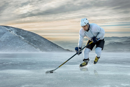 sportsmanship: Ice hockey player on the ice in mountains Stock Photo