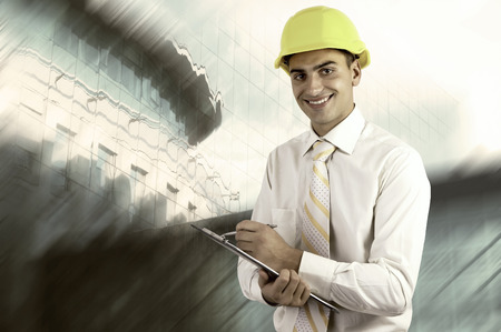 Young architect wearing a protective helmet standing on the building outdoor background photo