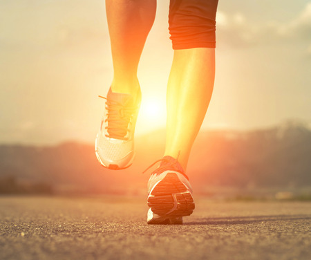 Runner athlete feet running on road under sunlight. Stock Photo