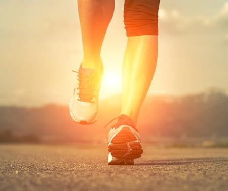 sunbeam: Runner athlete feet running on road under sunlight. Stock Photo