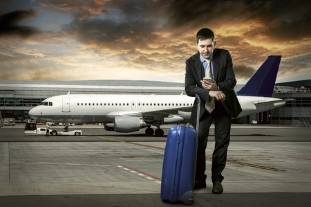 airport window: Businessman with baggage in airport Stock Photo