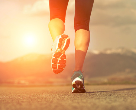 Runner athlete feet running on road under sunlight. photo