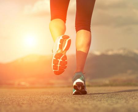 young woman running: Runner athlete feet running on road under sunlight. Stock Photo