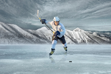 hockey stick: Ice hockey player on the ice in mountains Stock Photo
