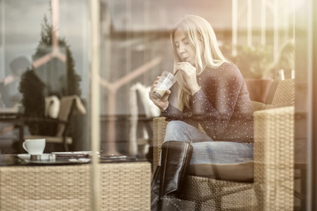 through: Happiness female with coffee. View through glass.