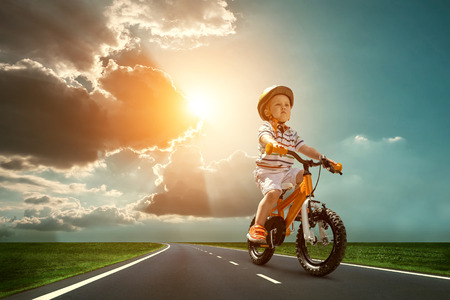 healthy people: Child seating on the orange bicycle and travelling on the non-urban road under sky