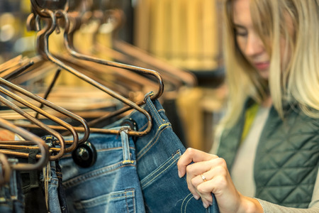 Beautiful blonde female looking jeans in the boutique Stock Photo