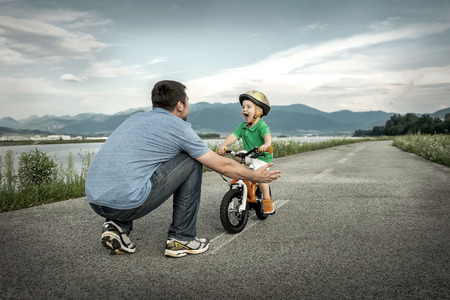 personas saludables: Padre e hijo en la bicicleta al aire libre