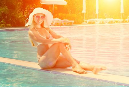 waterpool: Beautiful female in white bikini seating near the waterpool under sun light