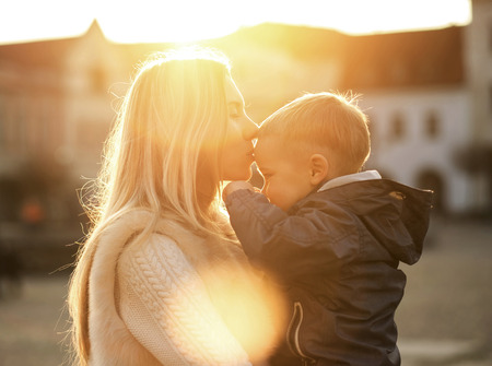 Happiness mother and son on the street at sunny day Stock Photo