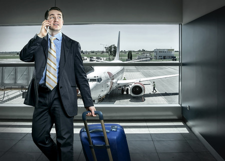 Businessman with baggage in airport Imagens