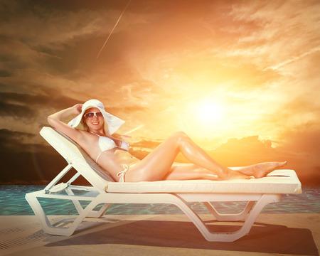 waterpool: Beautiful female in white bikini near the waterpool under sun light