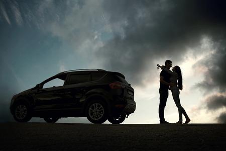 parejas enamoradas: Silueta de la felicidad pareja alojarse cerca del nuevo coche bajo el cielo