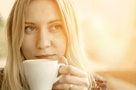 Female with coffee at cafe under sunlight