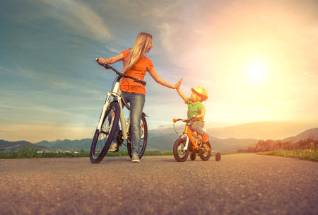 the mother: Happiness Mother and son on the bicycles funning outdoor Stock Photo