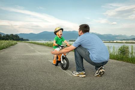 andando en bicicleta: Padre e hijo en la bicicleta al aire libre