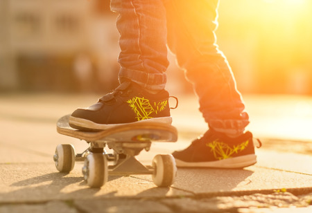 skateboard shoes: Child with skateboard on the street at sunset light. Stock Photo