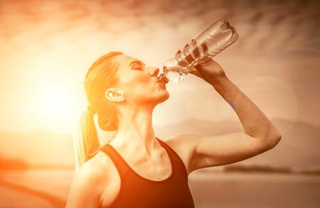 agua potable: Hermosa hembra después de correr, beber agua bajo el cielo