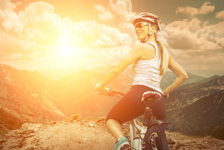 bicycle helmet: Beautiful woman in helmet and glasses stay on the bicycle around mountains.